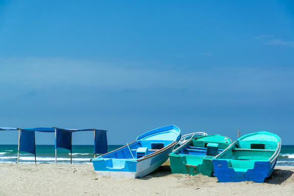 Blue boats, blue sky, blue tents, and blue water on the beach of Canoa, Ecuador