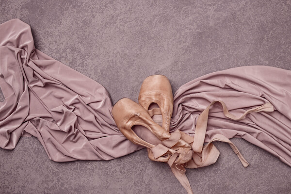 Ballet pointe shoes on pink studio background.
